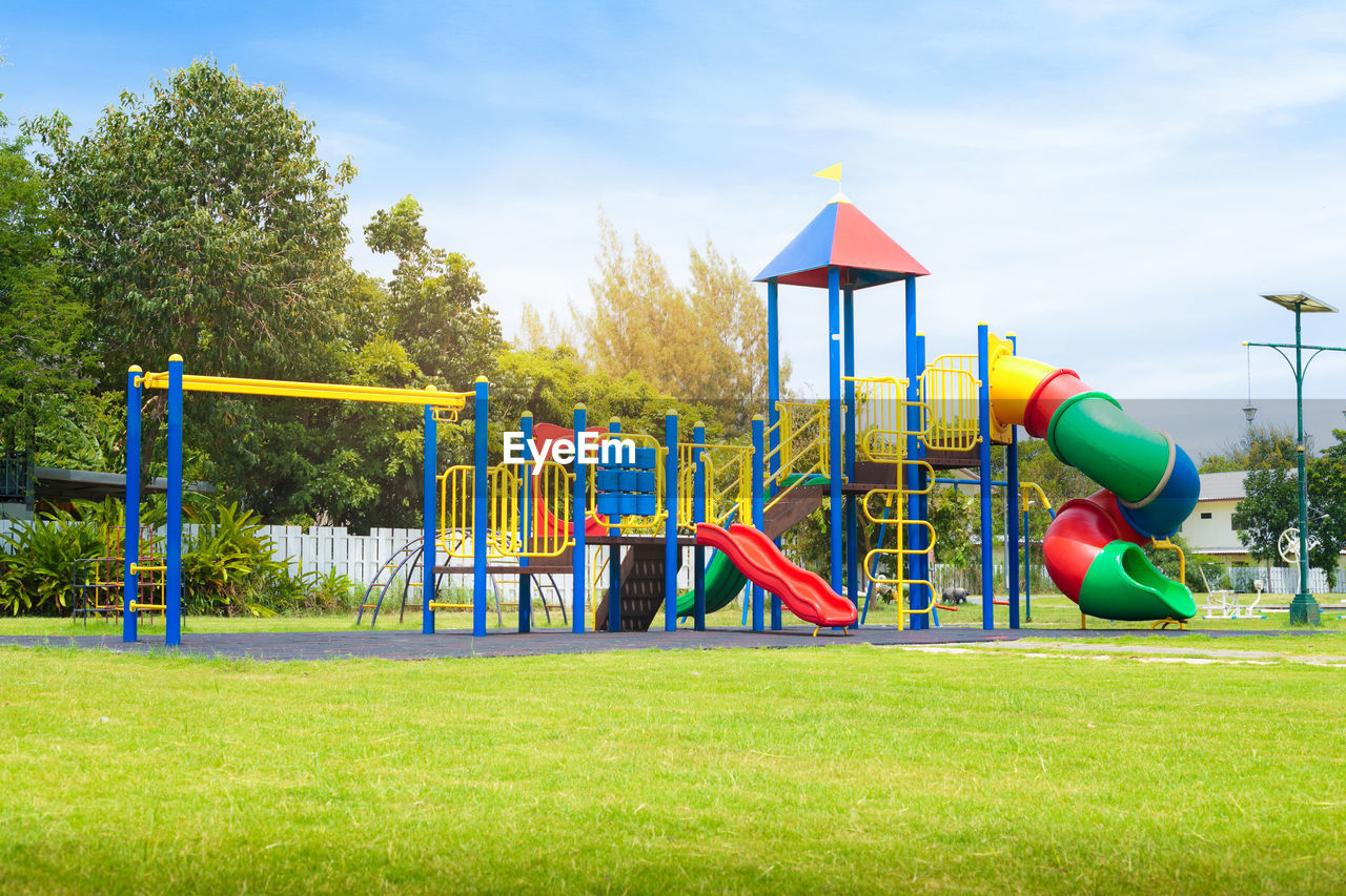 childhood, plant, playground, green color, day, slide - play equipment, outdoor play equipment, tree, multi colored, grass, nature, fun, sky, park, outdoors, park - man made space, blue, sunlight, leisure activity, jungle gym