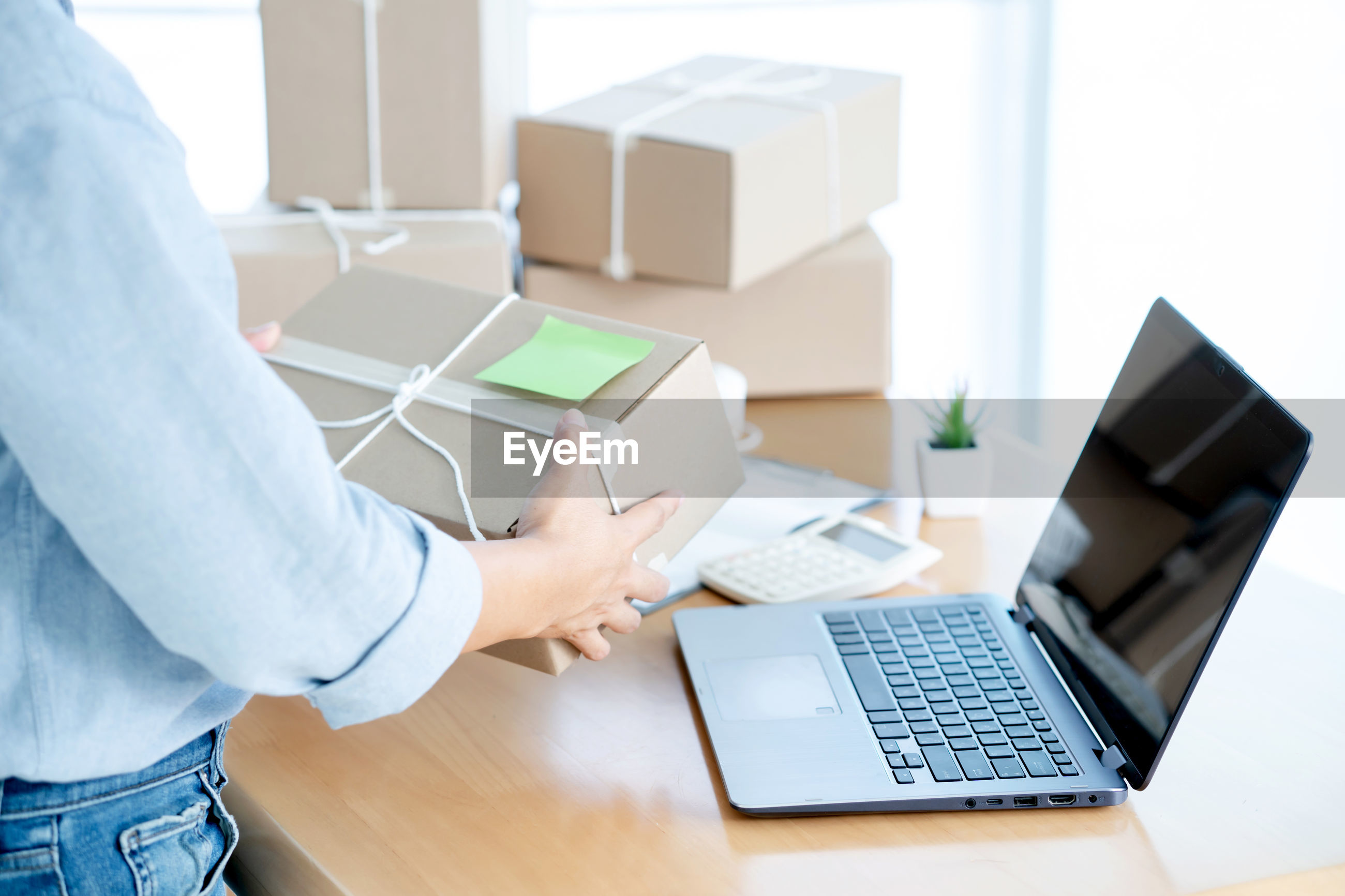 Midsection of man carrying box in office