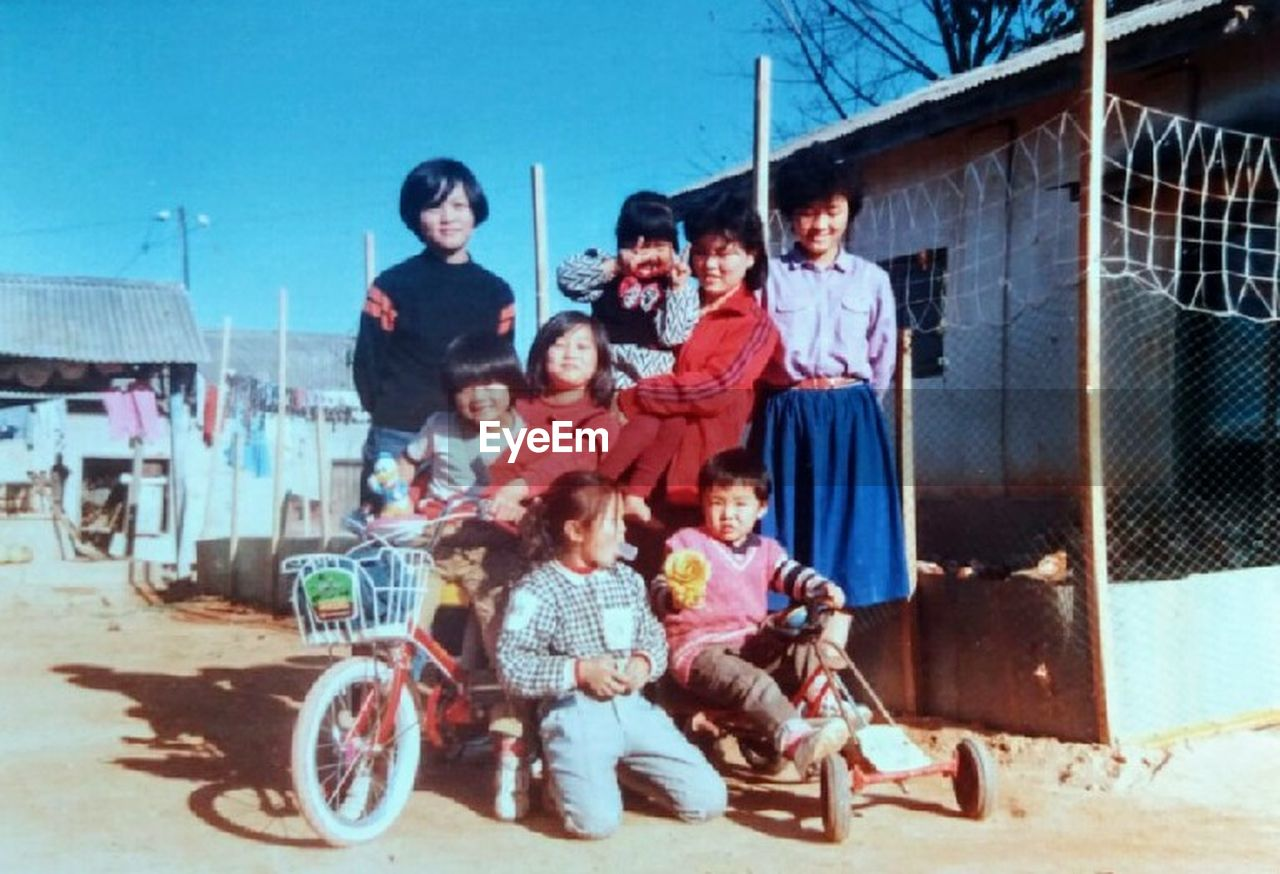 full length, boys, sitting, mid adult, child, son, group of people, father, adult, togetherness, mid adult men, mother, people, childhood, outdoors, girls, men, medium group of people, day, building exterior, portrait, young adult, women, looking at camera, males, smiling, city, cheerful, bonding, sky