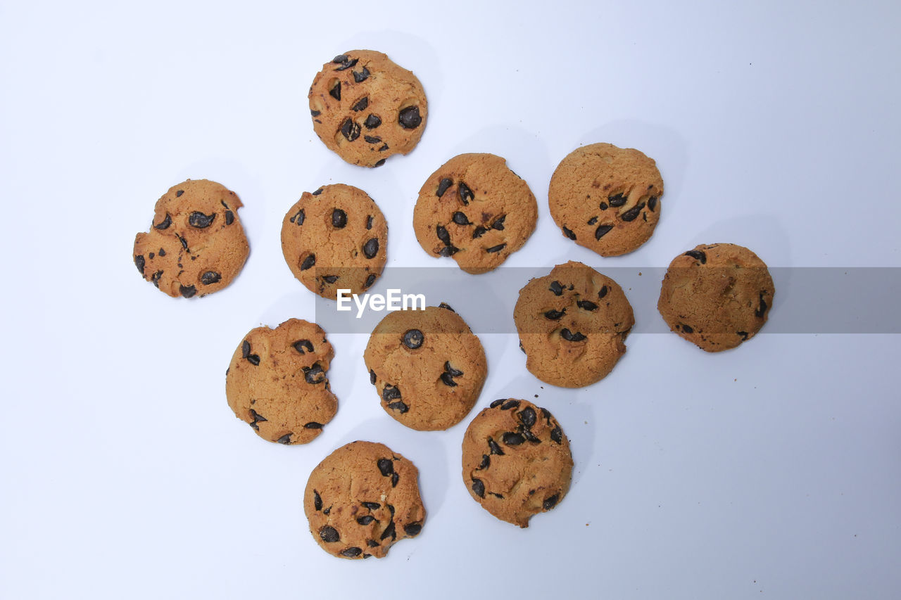 studio shot, white background, cookie, food and drink, indoors, food, still life, baked, freshness, no people, chocolate chip cookie, chocolate, sweet food, group of objects, brown, chocolate chip, high angle view, indulgence, close-up, unhealthy eating, temptation, snack