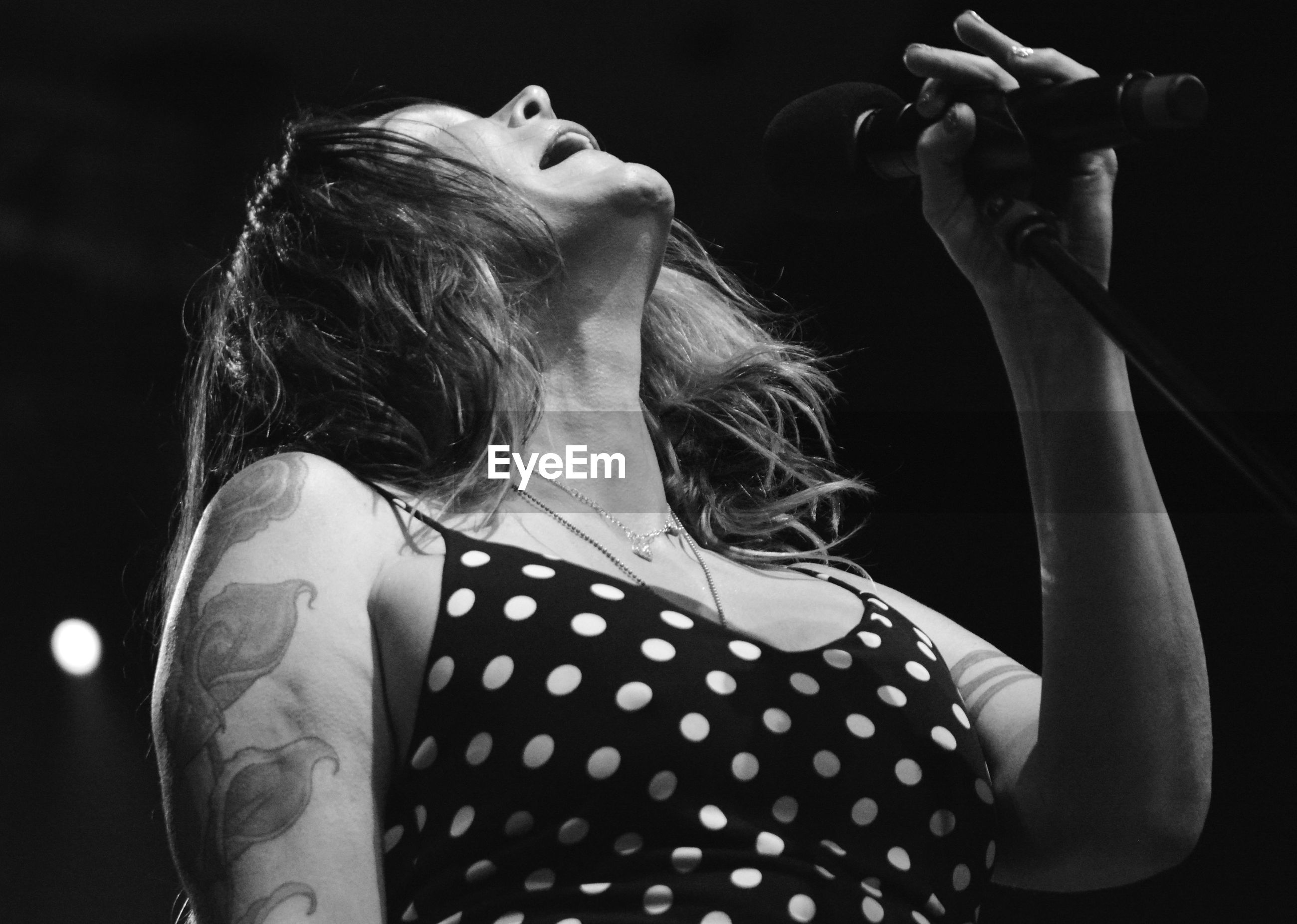Low angle view of woman singing in concert