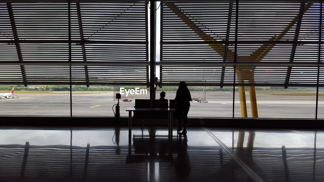 SILHOUETTE PEOPLE SITTING ON AIRPORT