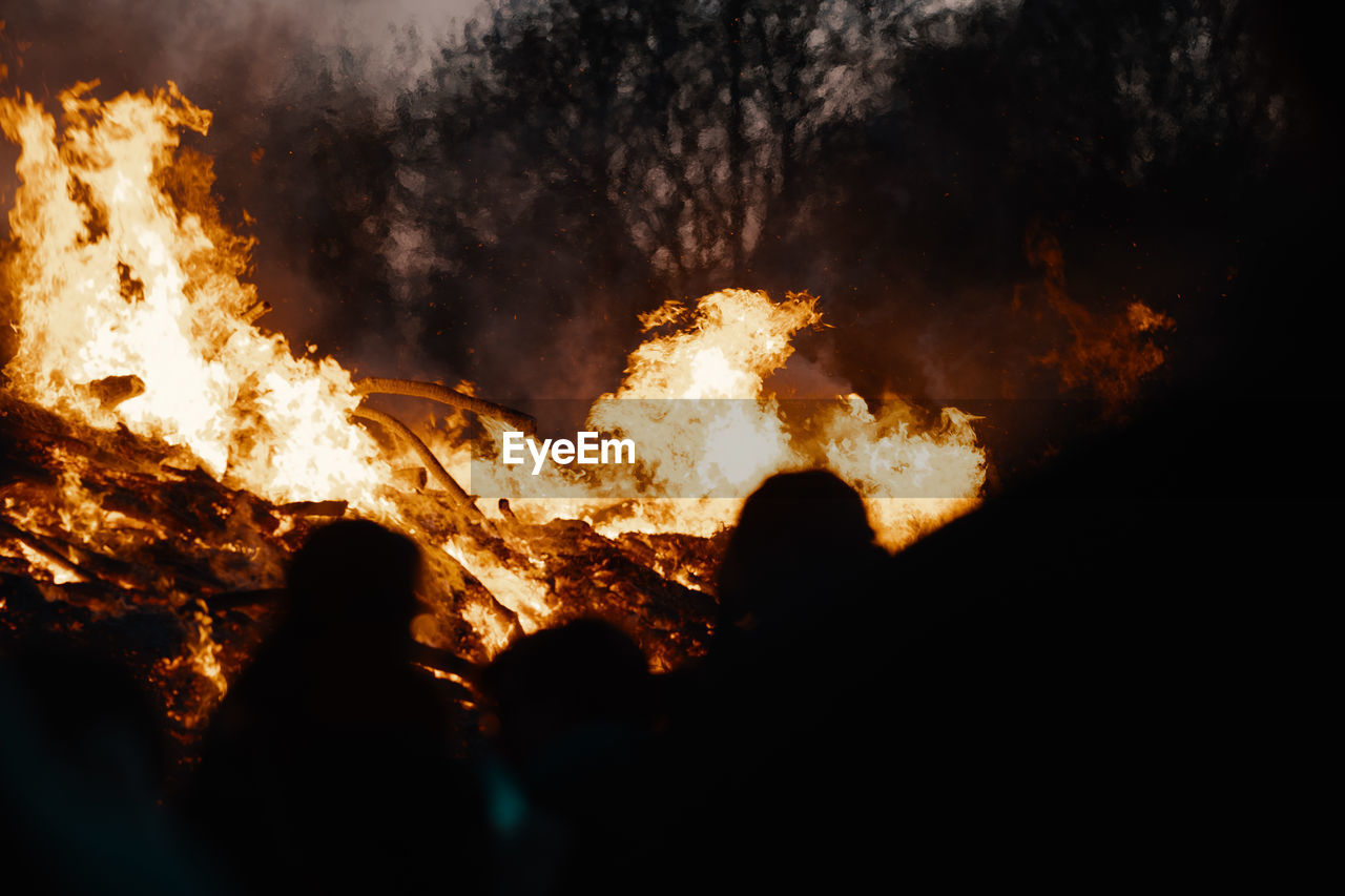 burning, fire, flame, heat - temperature, fire - natural phenomenon, night, real people, nature, glowing, accidents and disasters, orange color, warning sign, group of people, sign, motion, destruction, smoke - physical structure, outdoors, communication, silhouette, dark, bonfire