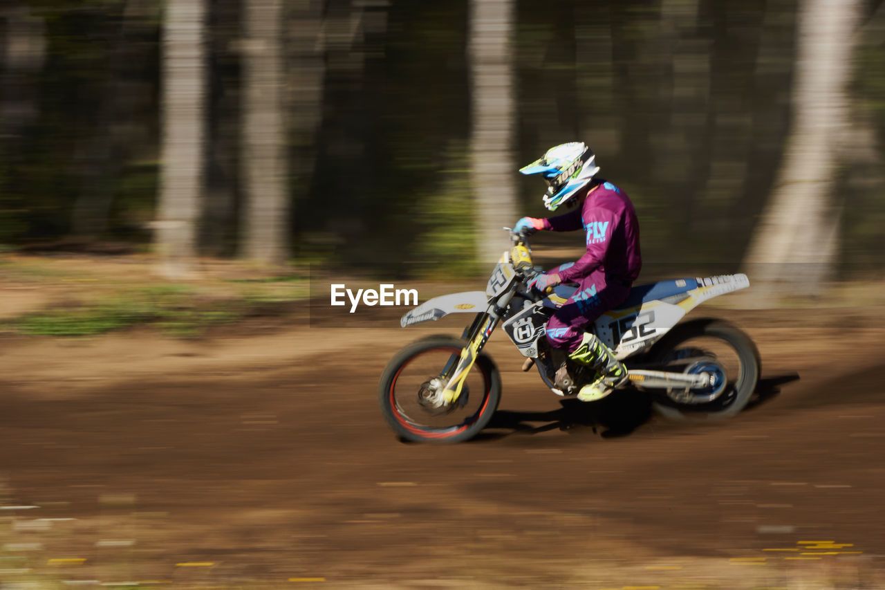 transportation, motion, mode of transportation, blurred motion, one person, land vehicle, sport, real people, helmet, speed, full length, day, riding, ride, road, lifestyles, on the move, leisure activity, nature, outdoors