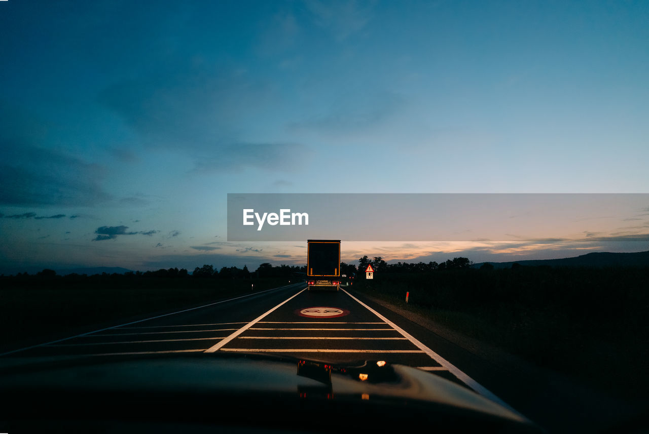 Car and truck moving on road against sky during sunset