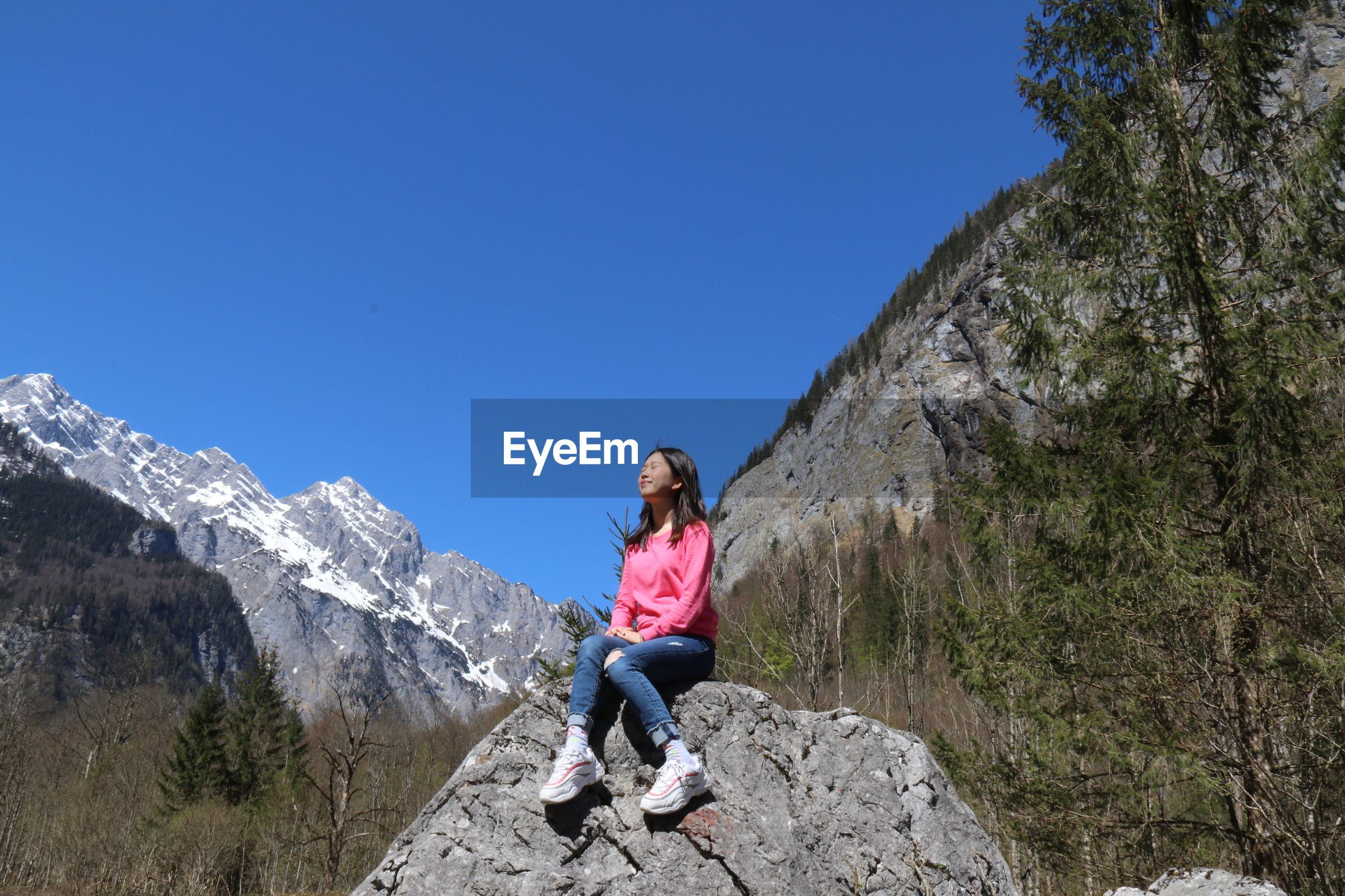 Full length of woman sitting on rock amidst mountain range against blue sky