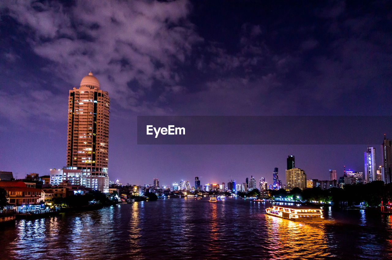 building exterior, built structure, architecture, water, sky, night, illuminated, city, building, waterfront, office building exterior, skyscraper, tall - high, cloud - sky, river, cityscape, landscape, reflection, nature, no people, modern, outdoors, financial district, luxury