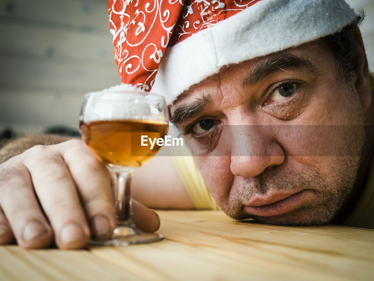 Close-up portrait of mature man wearing santa hat holding drink on table
