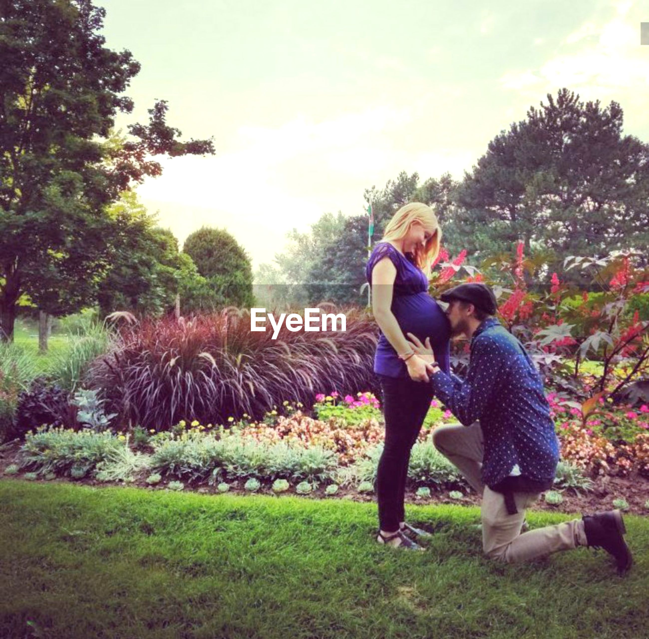 Side view of man kissing pregnant woman belly in park
