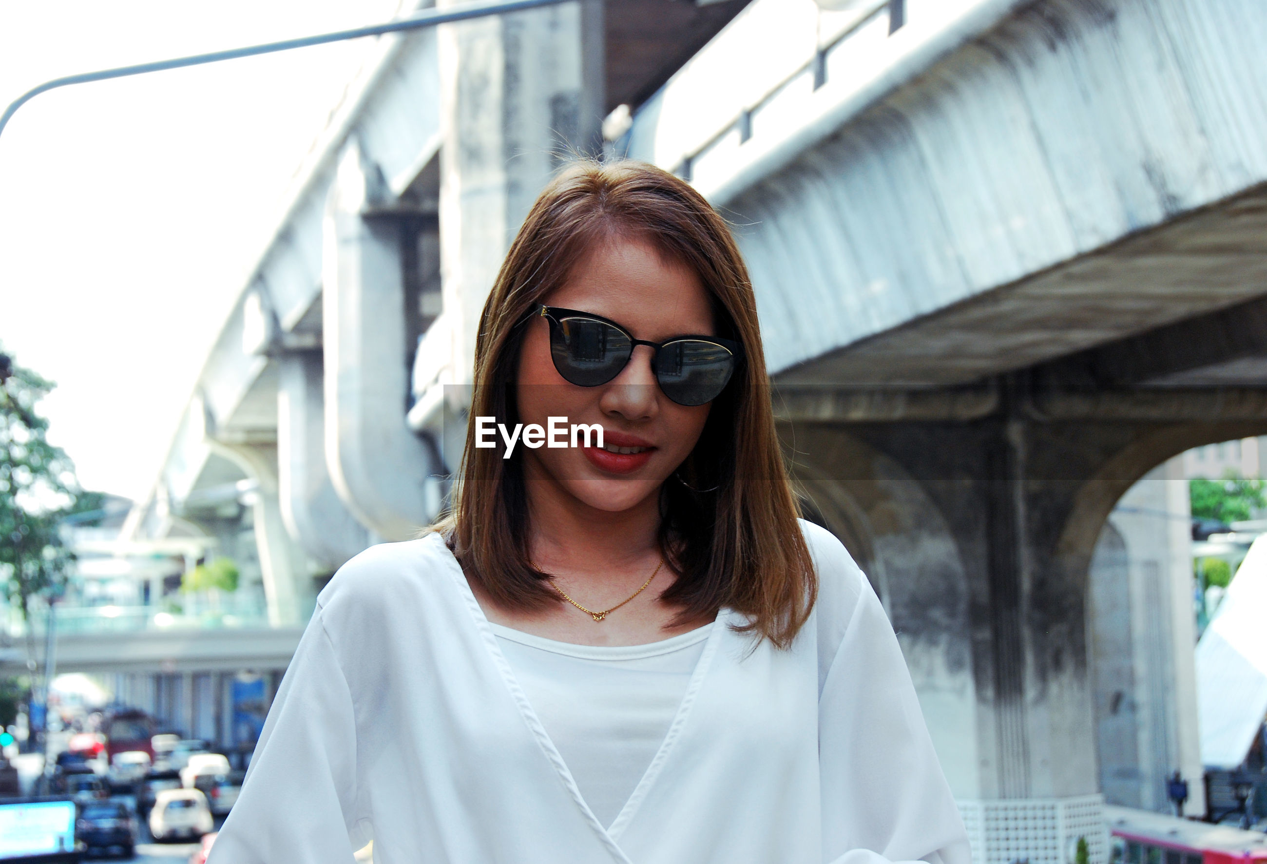 Portrait of young woman in sunglasses standing in city