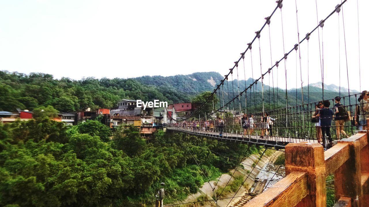 Bridge Leading Towards Village Amidst Trees Against Clear Sky