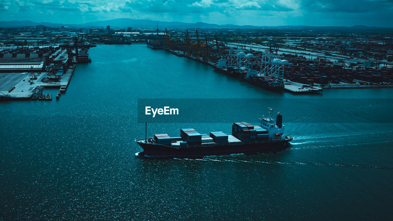 High angle view of shipping container sailing in sea and shipping terminal background cinematic