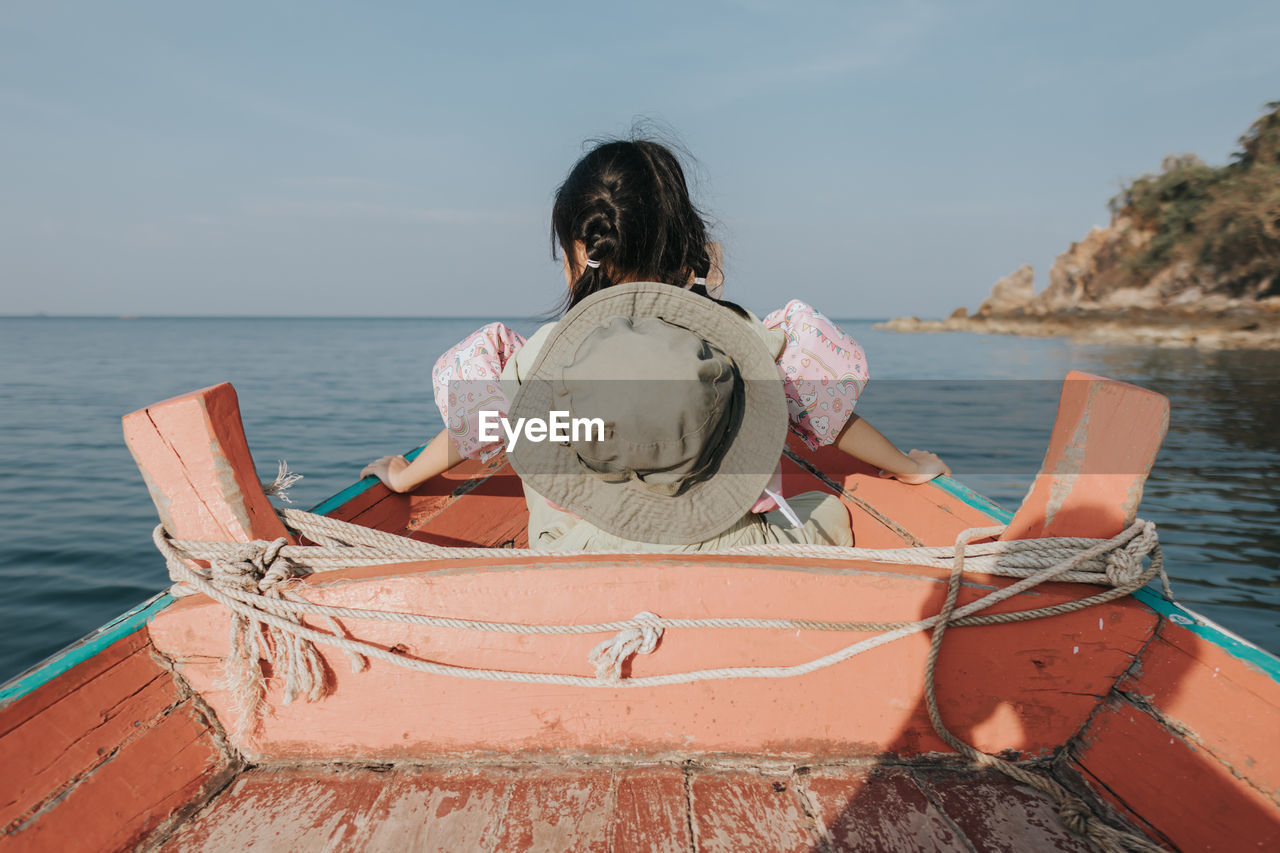 Little girl in the boat watching sea