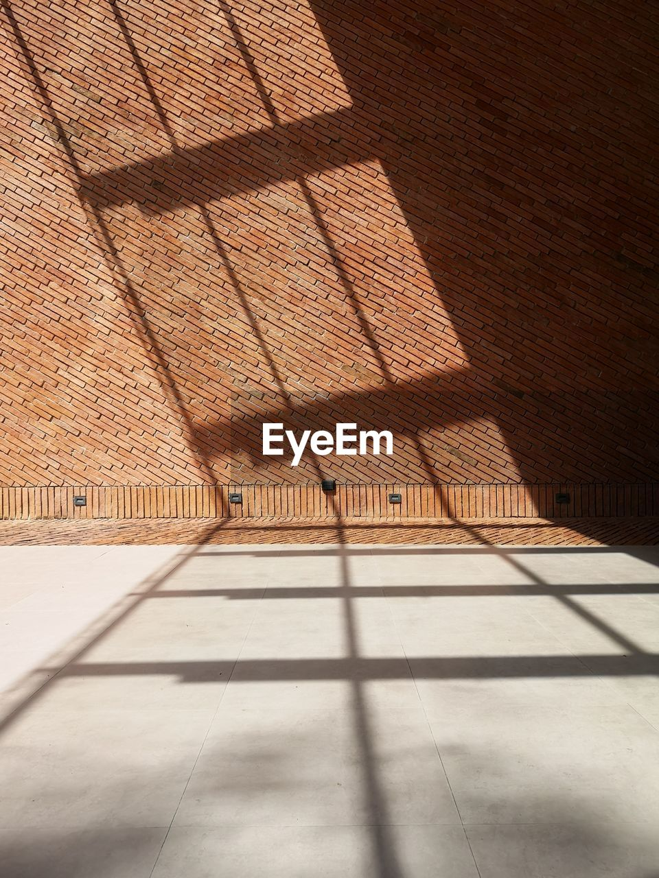 shadow, sunlight, architecture, built structure, no people, day, nature, flooring, wall - building feature, building, outdoors, absence, building exterior, brick, pattern, brick wall, wall, tile, roof, focus on shadow, tiled floor