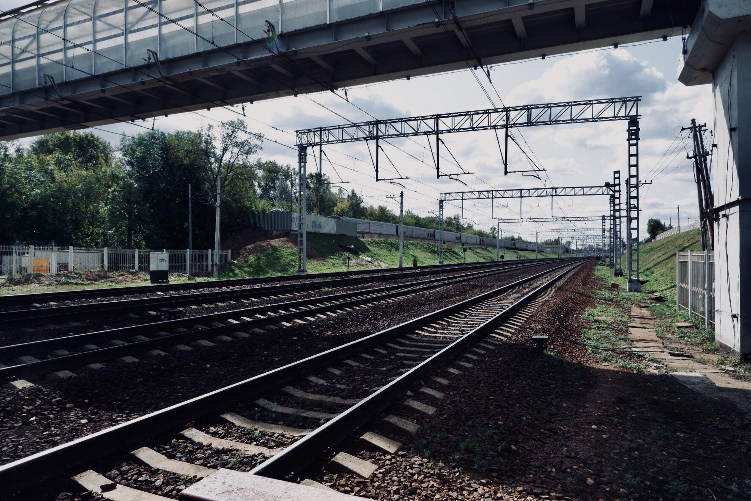 Bridge over railroad tracks against sky