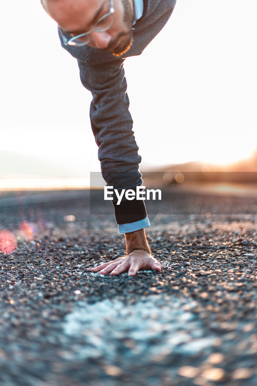 one person, low section, real people, selective focus, lifestyles, nature, day, human body part, sky, body part, human leg, leisure activity, beach, standing, casual clothing, outdoors, shoe, sunlight, road, jeans, surface level, human limb, pebble, human foot