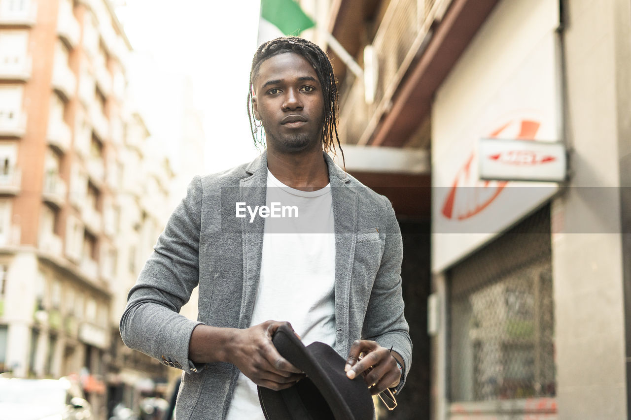 PORTRAIT OF YOUNG MAN STANDING AGAINST WALL IN CITY
