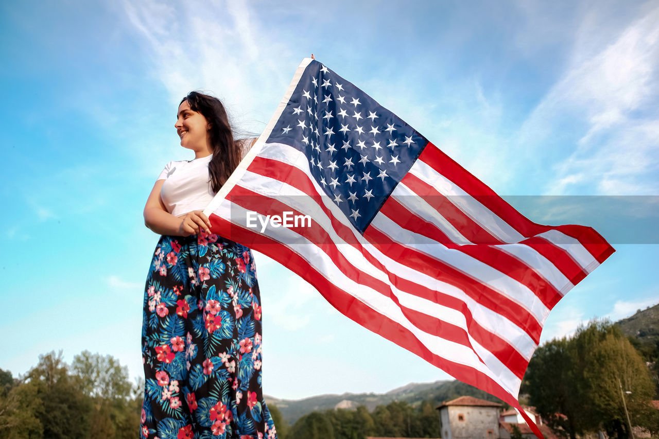 LOW ANGLE VIEW OF PERSON STANDING AGAINST FLAG