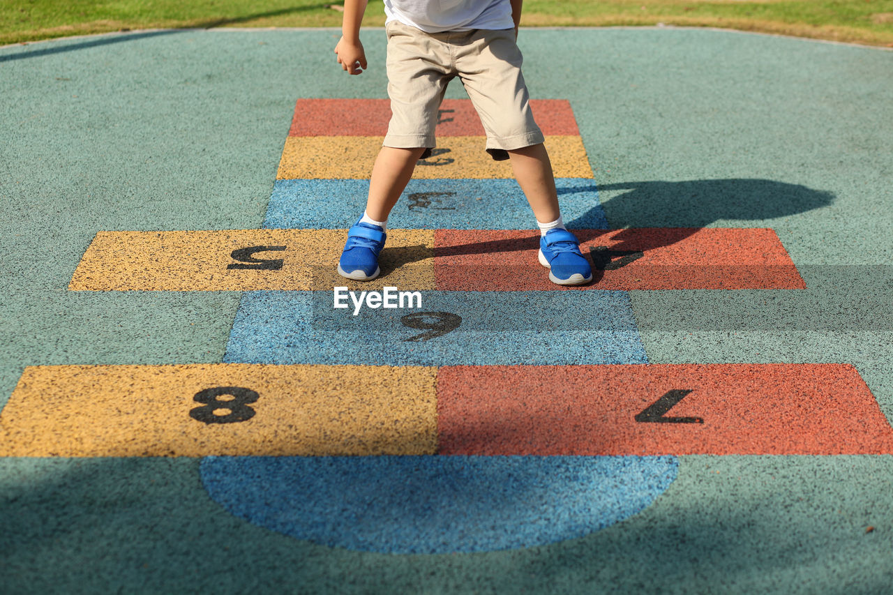 Low Section Of Boy Playing Hopscotch At Playground
