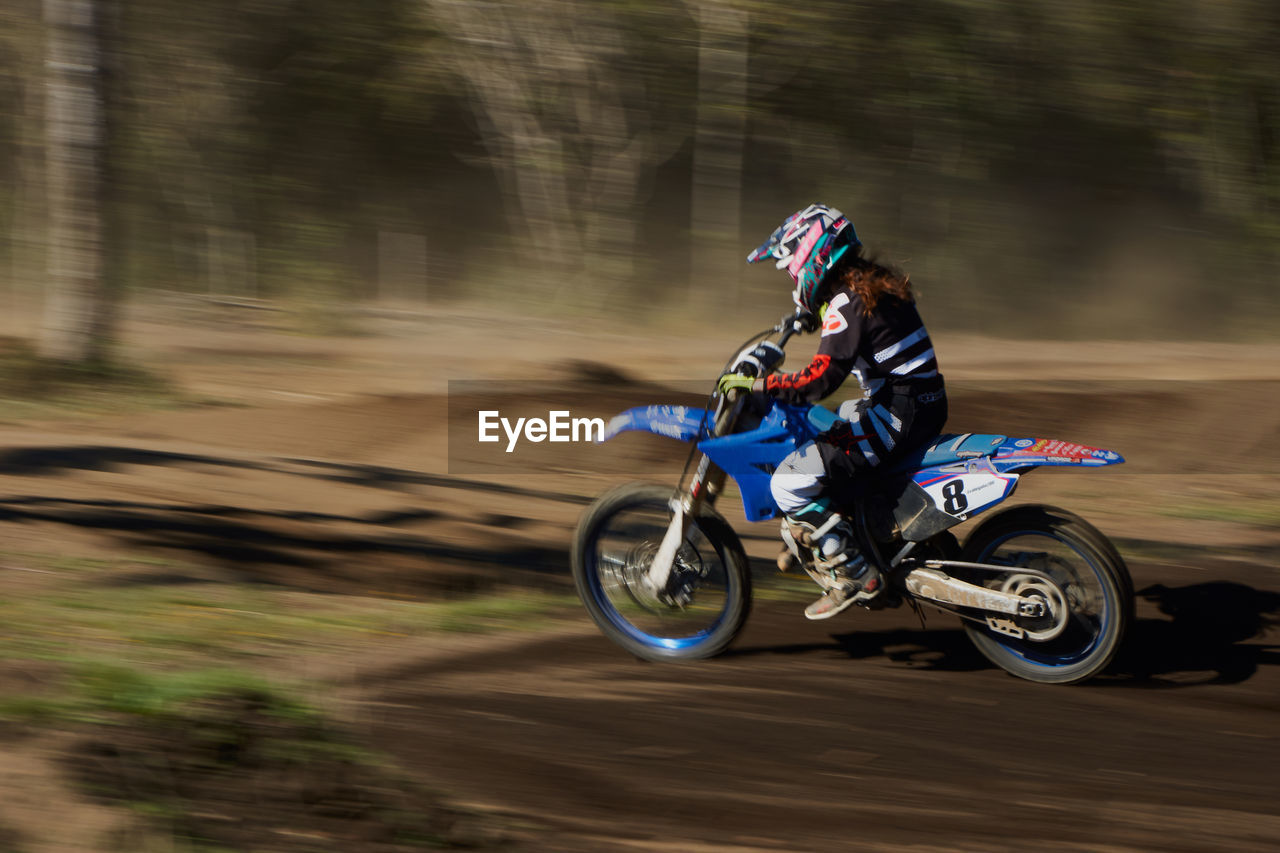 transportation, mode of transportation, motion, blurred motion, motorcycle, riding, ride, speed, land vehicle, road, sport, helmet, one person, real people, on the move, day, sports helmet, competition, headwear, motocross, outdoors, crash helmet, biker