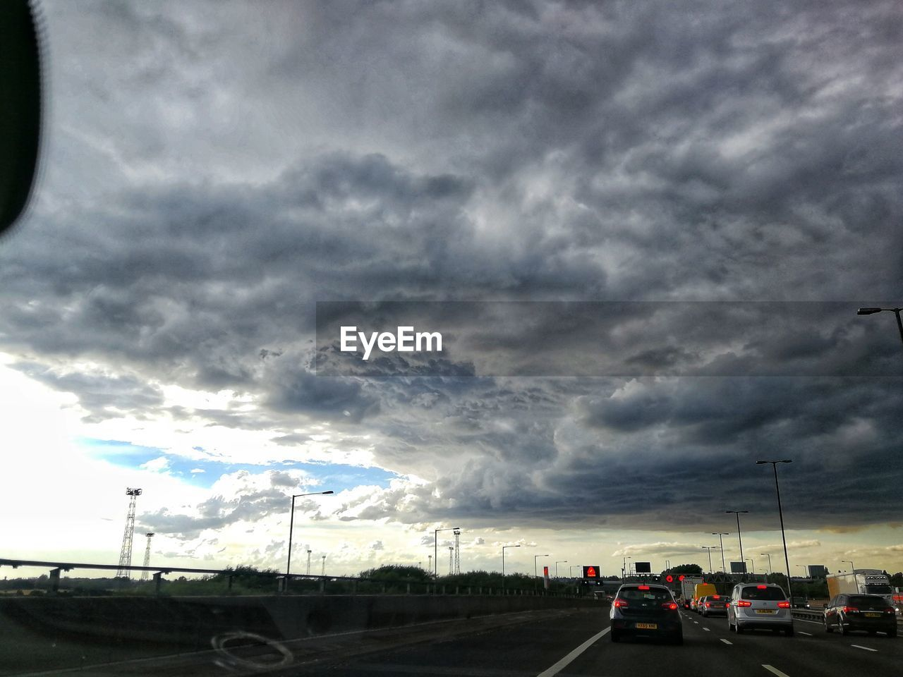 cloud - sky, sky, transportation, mode of transportation, road, motor vehicle, car, land vehicle, nature, storm, street, storm cloud, no people, overcast, dramatic sky, dusk, travel, cloudscape, highway, outdoors, ominous, road trip