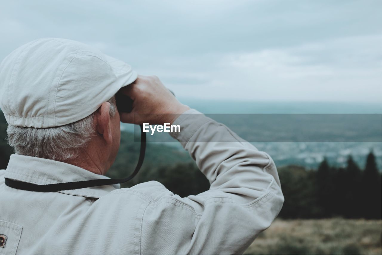 Rear view of senior man looking through binoculars while standing on mountain against cloudy sky