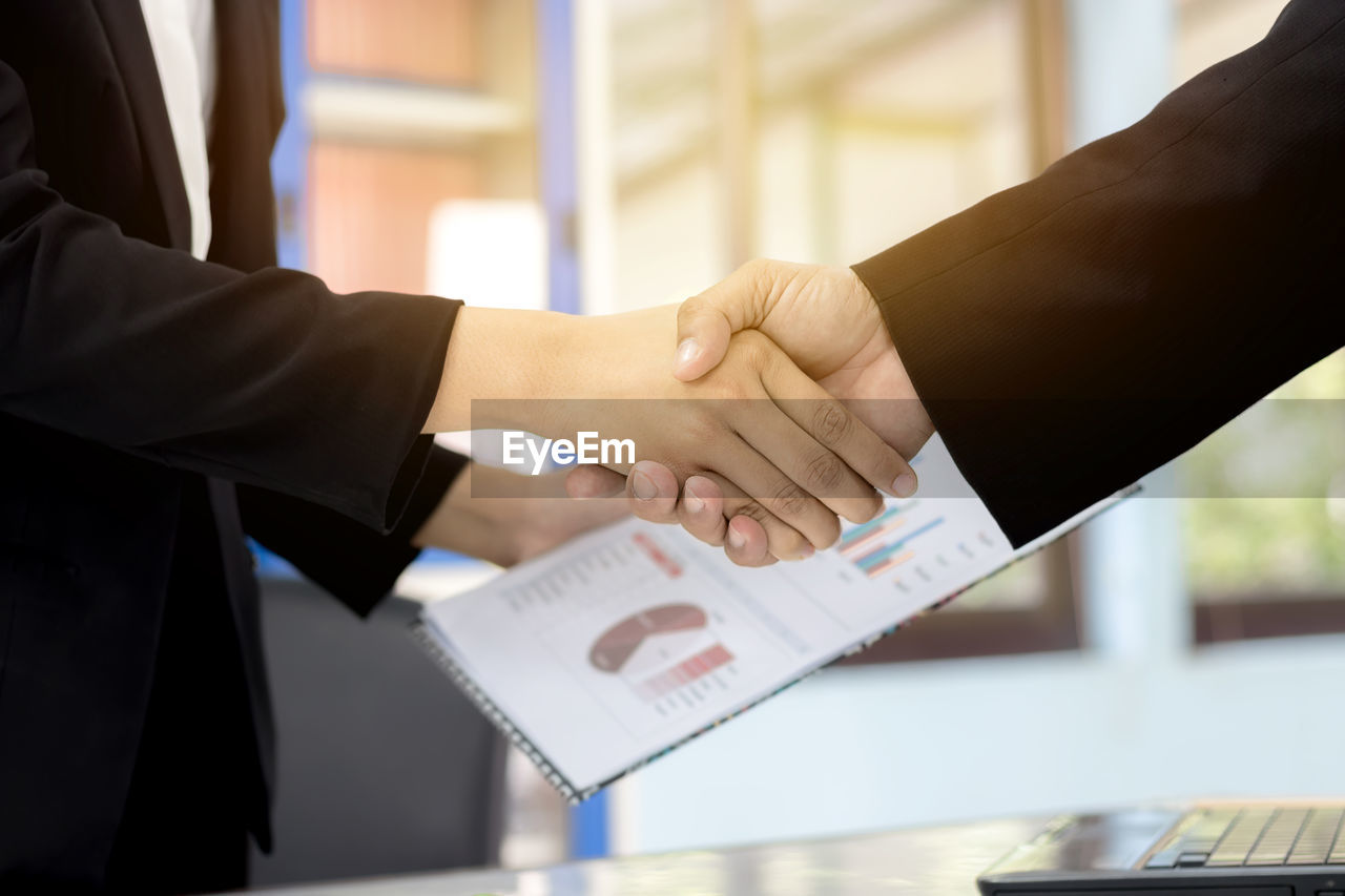 Midsection of woman holding chart while handshaking with colleague over office desk