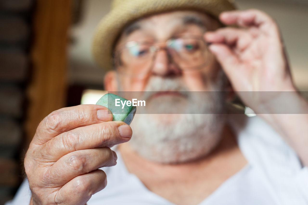 Close-Up Of Senior Man Holding Stone