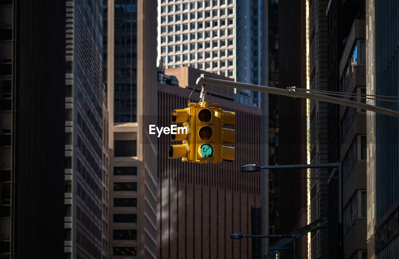 built structure, architecture, building exterior, building, city, stoplight, sign, road signal, no people, office building exterior, yellow, day, communication, road, outdoors, light, road sign, skyscraper, office, residential district, modern
