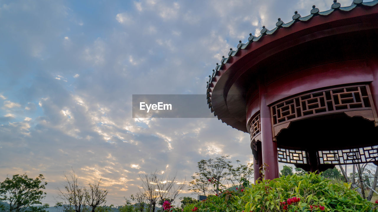 cloud - sky, sky, built structure, architecture, plant, nature, building exterior, low angle view, no people, day, tree, outdoors, flowering plant, flower, red, building, growth, arts culture and entertainment, beauty in nature, amusement park