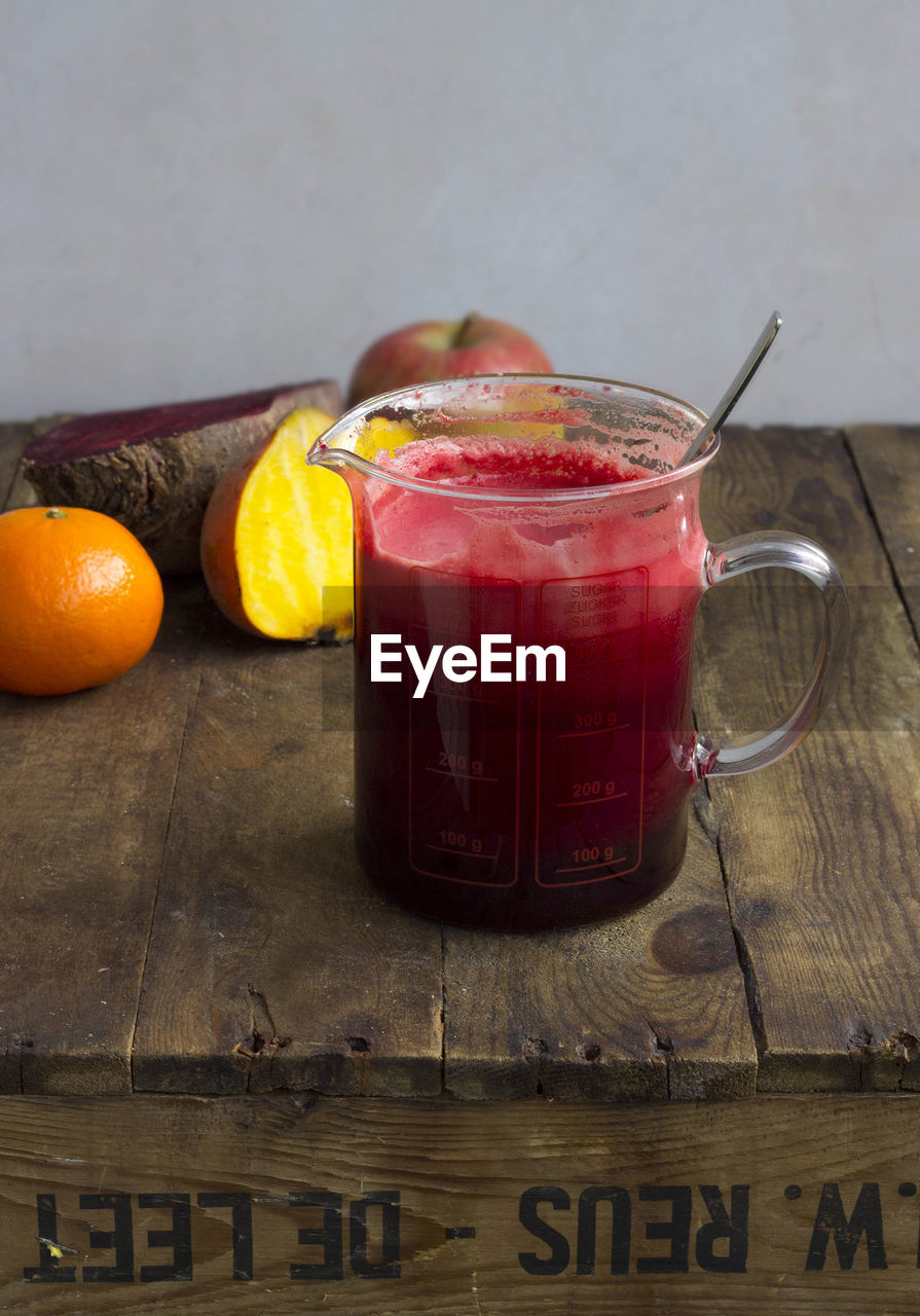 View of raw vegetable and fruit juice in measuring jug