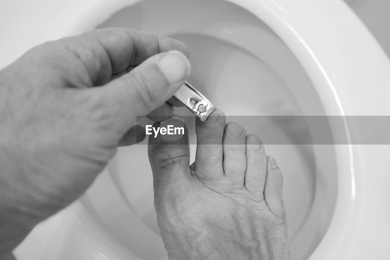 Man Clipping Toenails On Toilet Commode