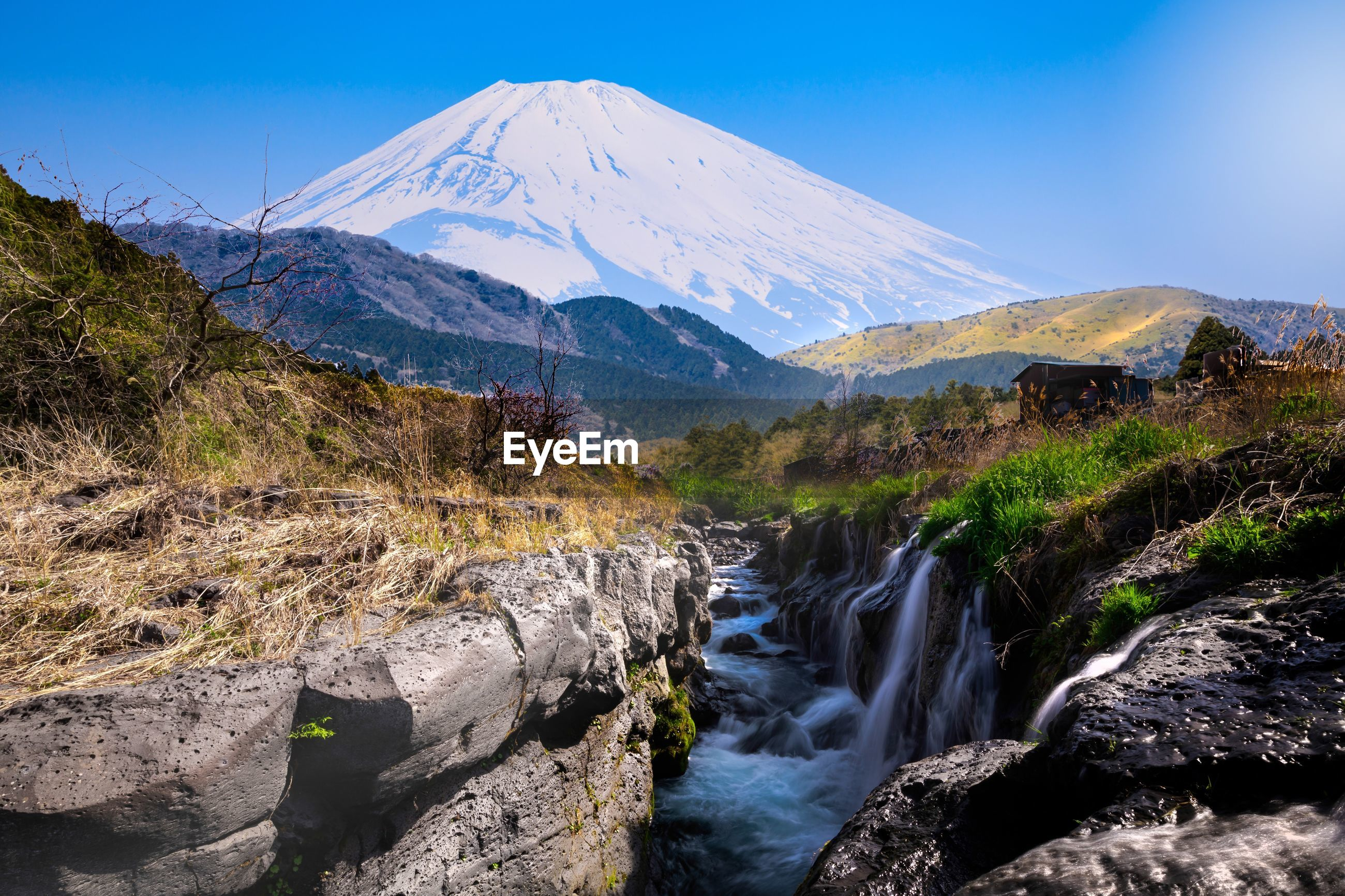 Scenic view of small waterfalls and fuji mountains blue sky background in japan