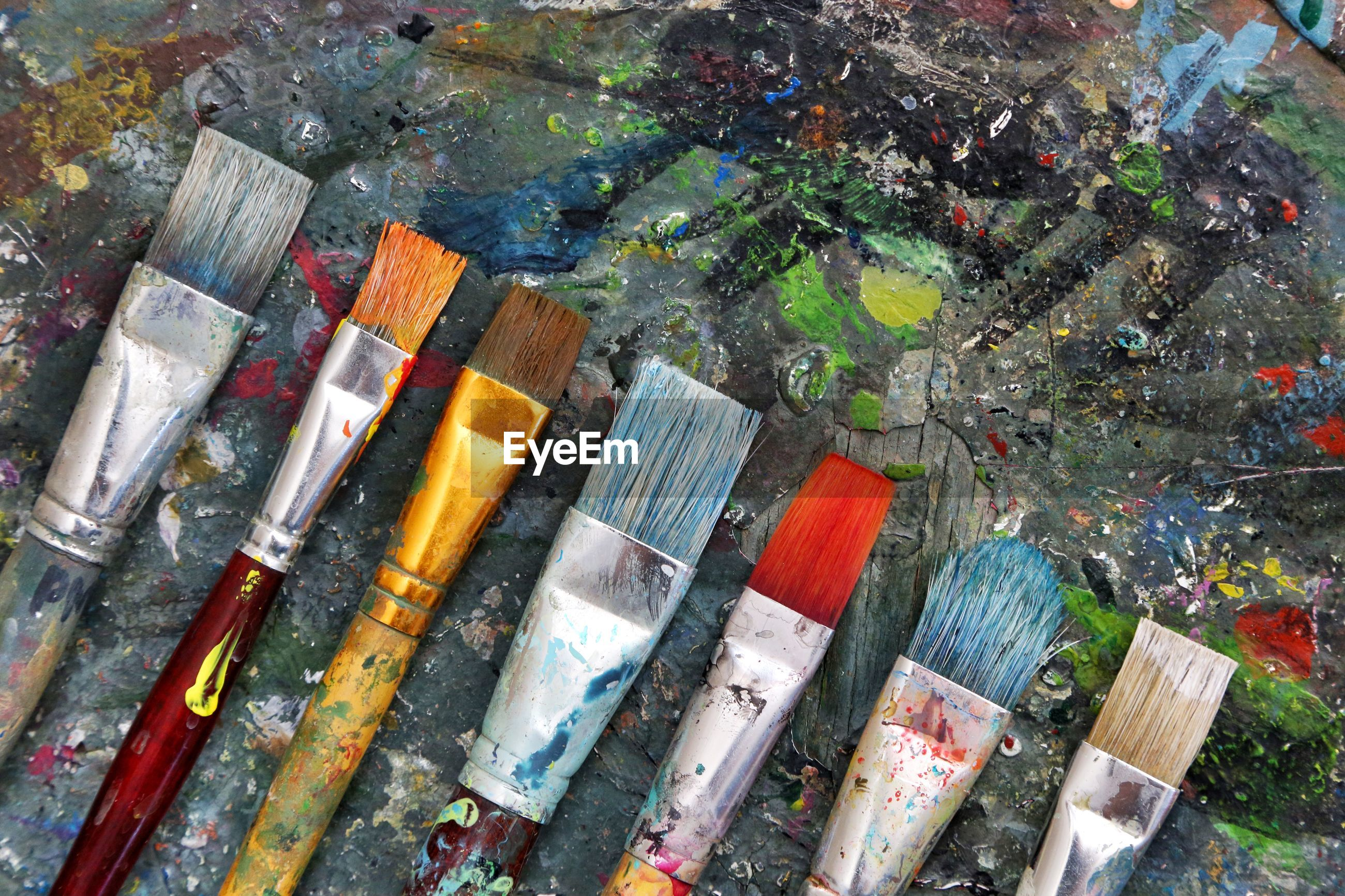 Close-up of paintbrushes on dirty table