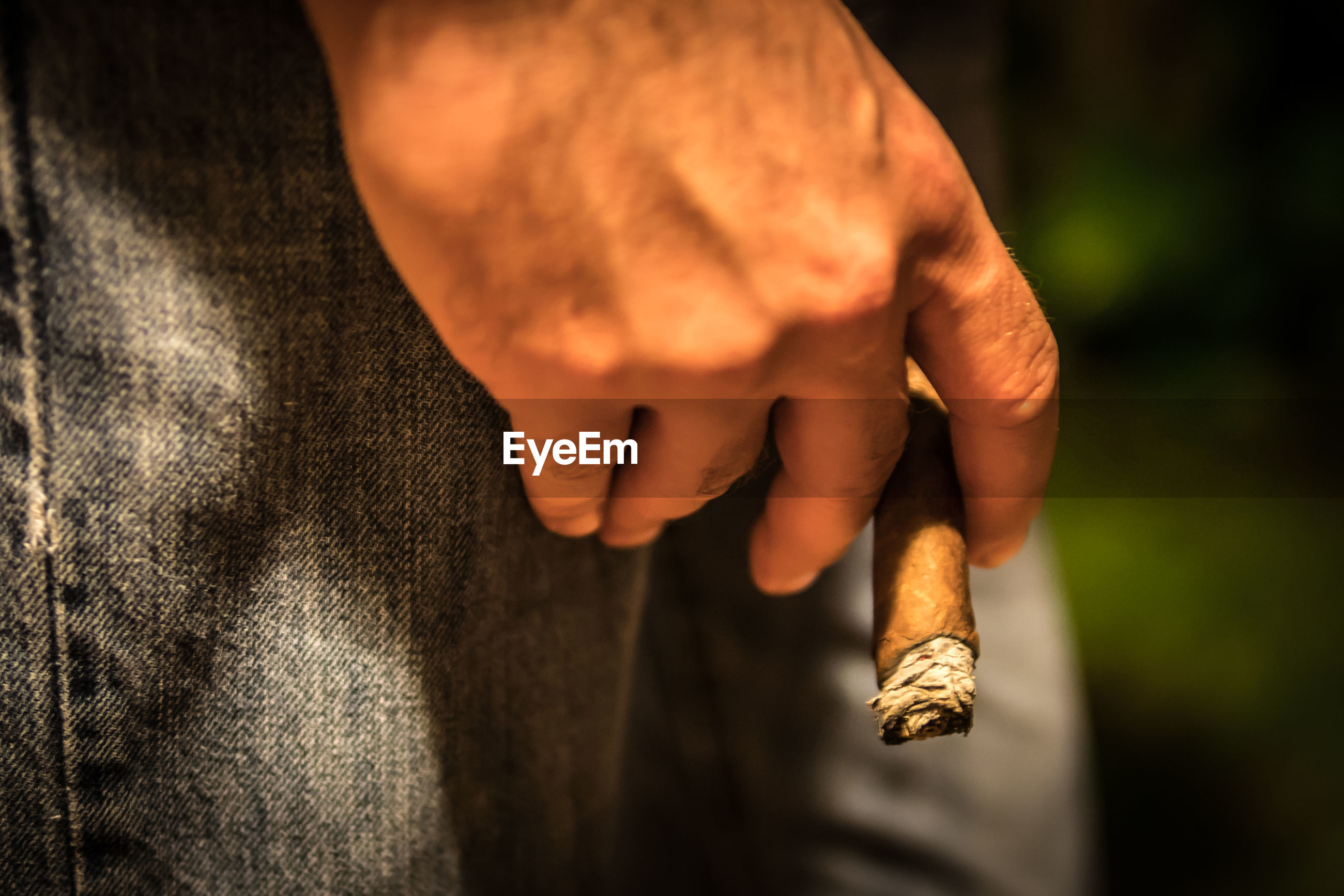 Midsection of man holding lit cigar