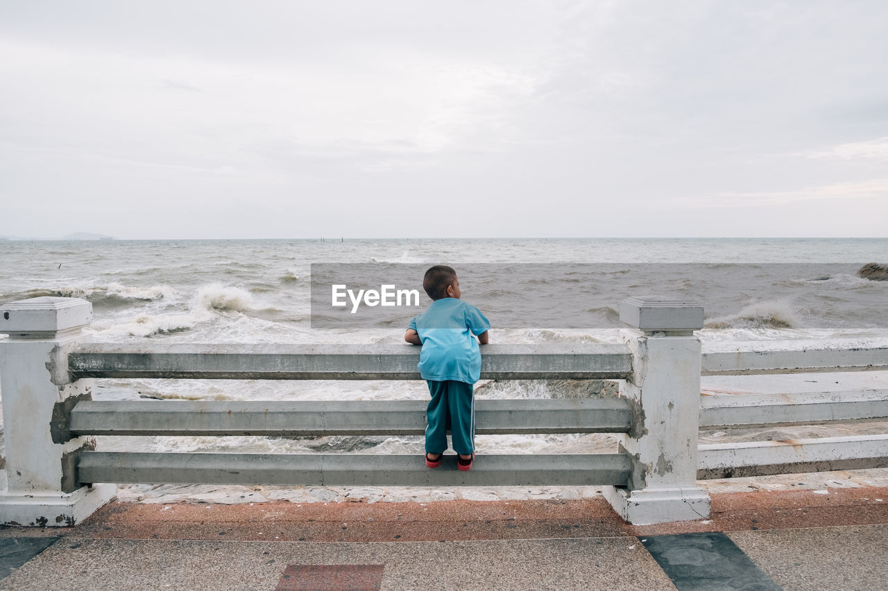 Rear view of boy looking at sea against sky