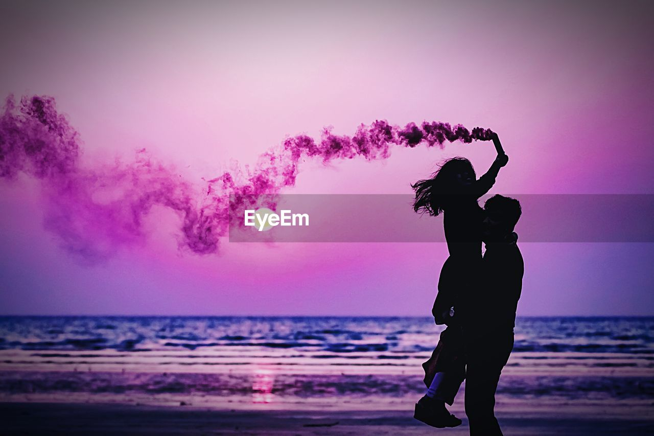 Silhouette Couple With Purple Distress Flare At Beach During Sunset