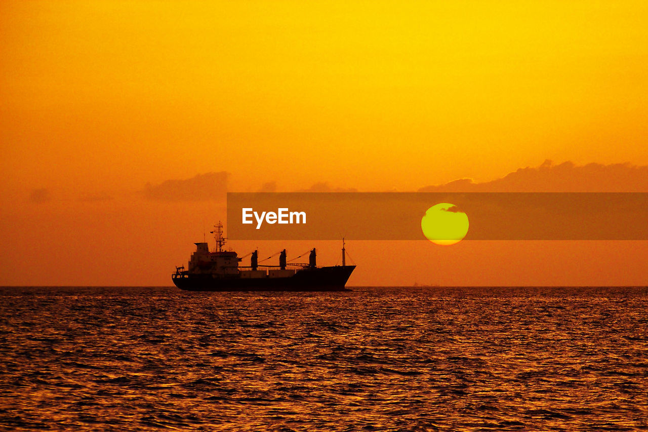 sunset, sea, orange color, silhouette, water, nautical vessel, sun, transportation, nature, beauty in nature, mode of transport, scenics, sky, waterfront, horizon over water, tranquility, outdoors, no people, sailing