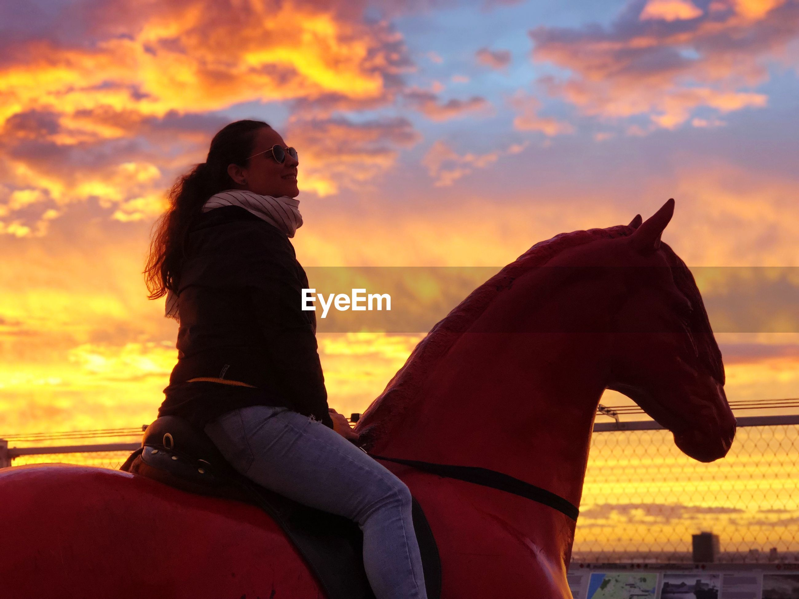 Woman sitting on horse statue against sky during sunset