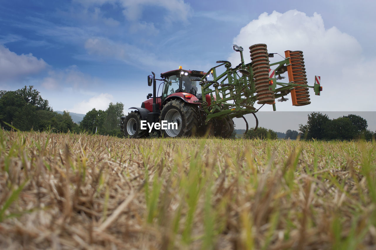 field, land, agriculture, growth, plant, farm, rural scene, nature, agricultural machinery, land vehicle, landscape, sky, day, crop, transportation, cloud - sky, mode of transportation, environment, tractor, agricultural equipment, outdoors, plantation