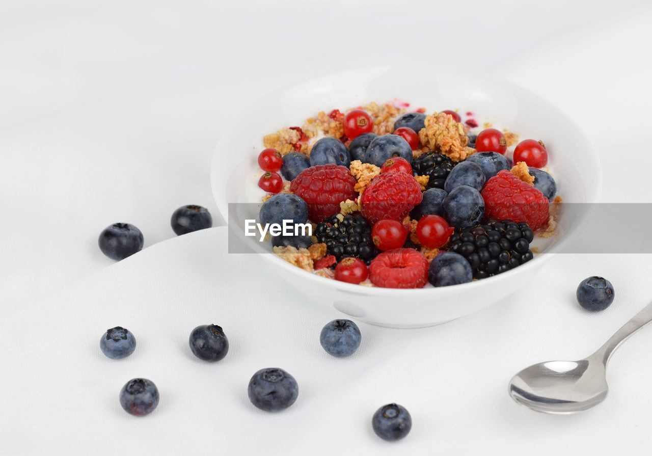 berry fruit, food, food and drink, blueberry, freshness, healthy eating, fruit, wellbeing, indoors, white background, still life, bowl, eating utensil, spoon, kitchen utensil, raspberry, table, studio shot, high angle view, close-up, no people, breakfast, temptation, red currant