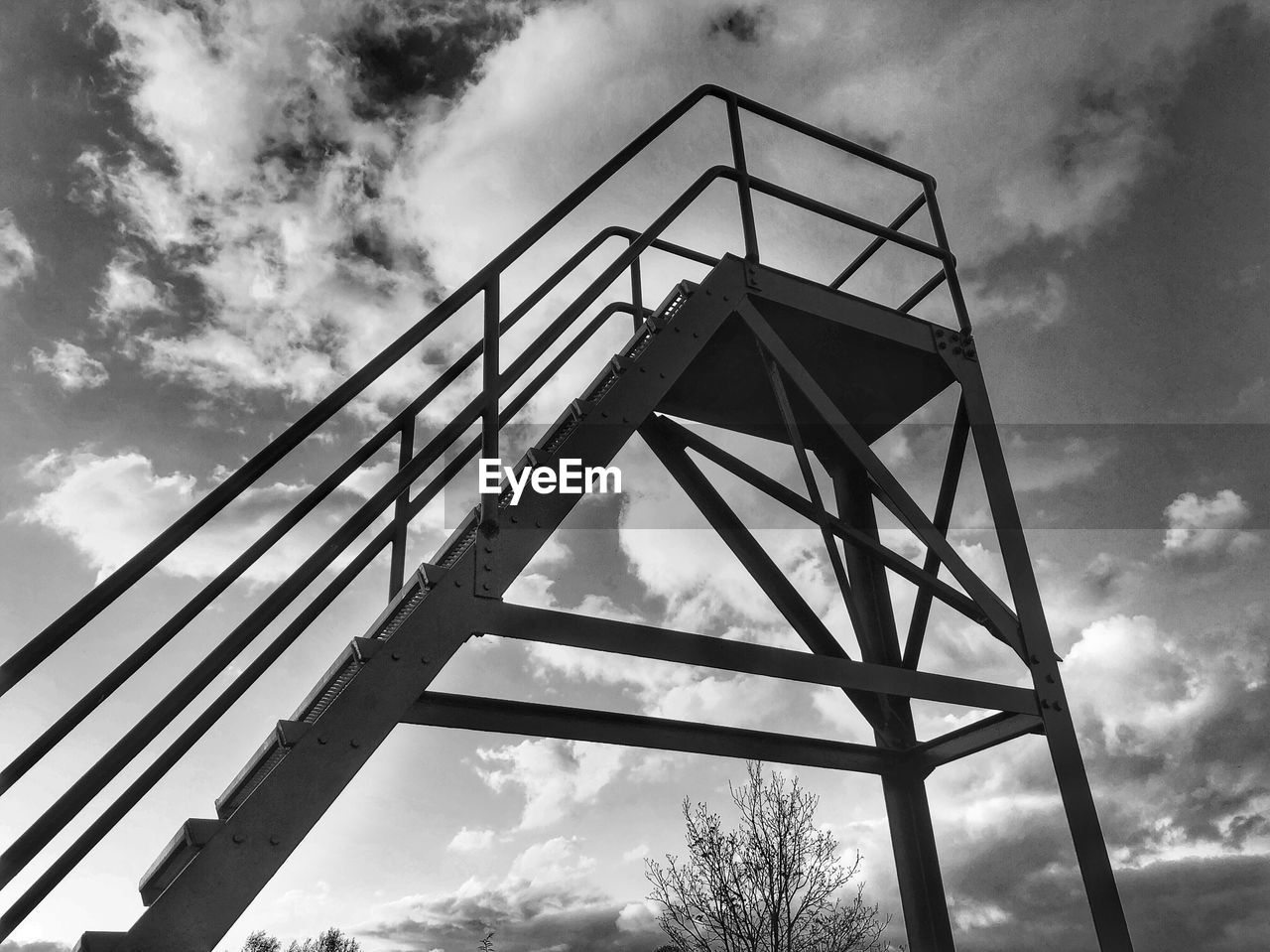 cloud - sky, low angle view, sky, architecture, built structure, nature, day, no people, outdoors, metal, bridge, connection, bridge - man made structure, silhouette, tree, staircase, railing, overcast, pattern