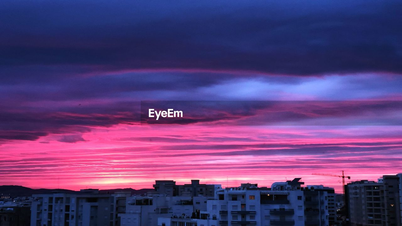 cloud - sky, sky, building exterior, architecture, built structure, sunset, building, city, no people, nature, dramatic sky, pink color, orange color, residential district, dusk, beauty in nature, outdoors, silhouette, cityscape, purple, romantic sky, ominous