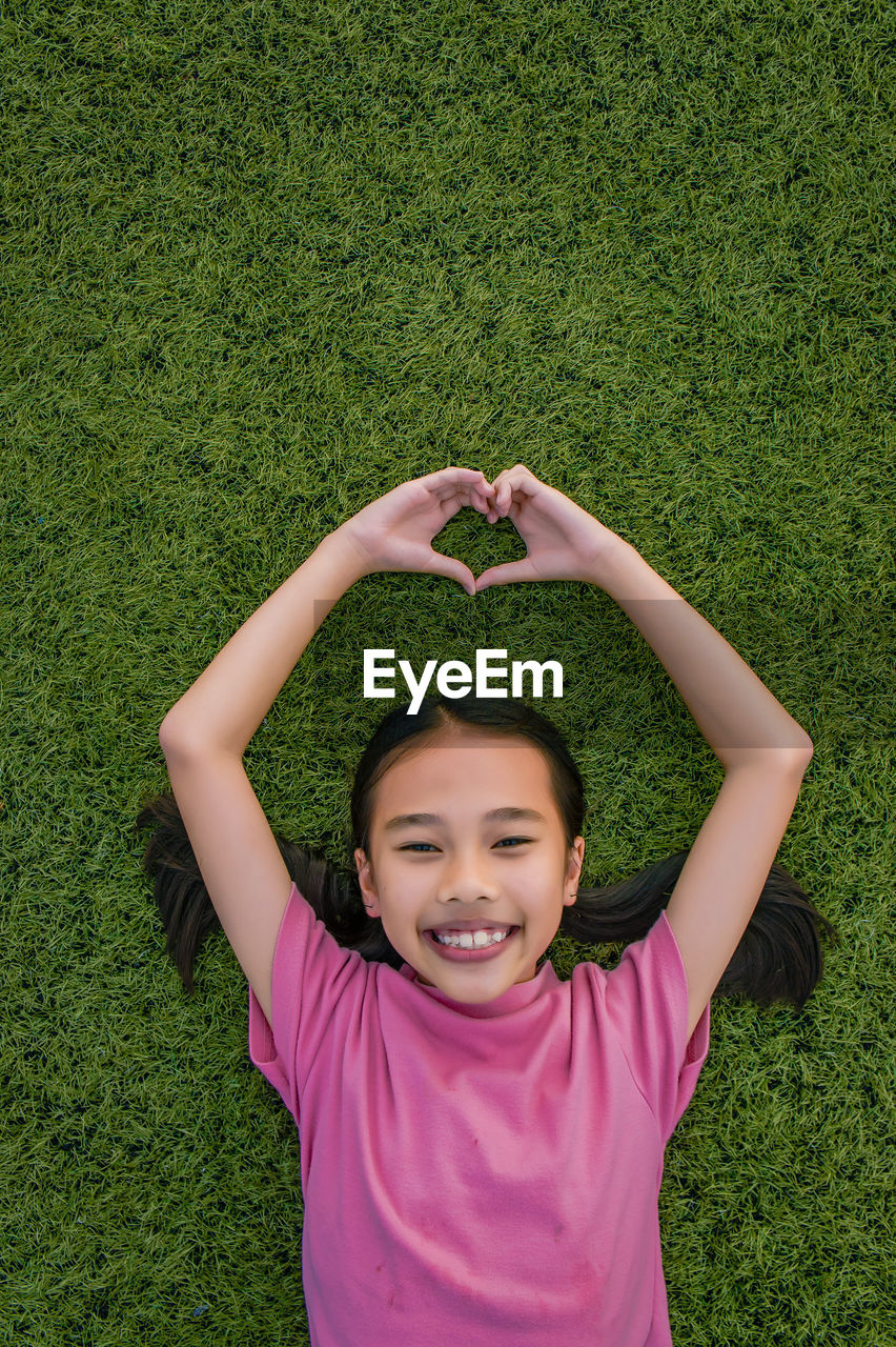 Portrait Of Smiling Girl With Arms Raised Gesturing Heart Shape On Field