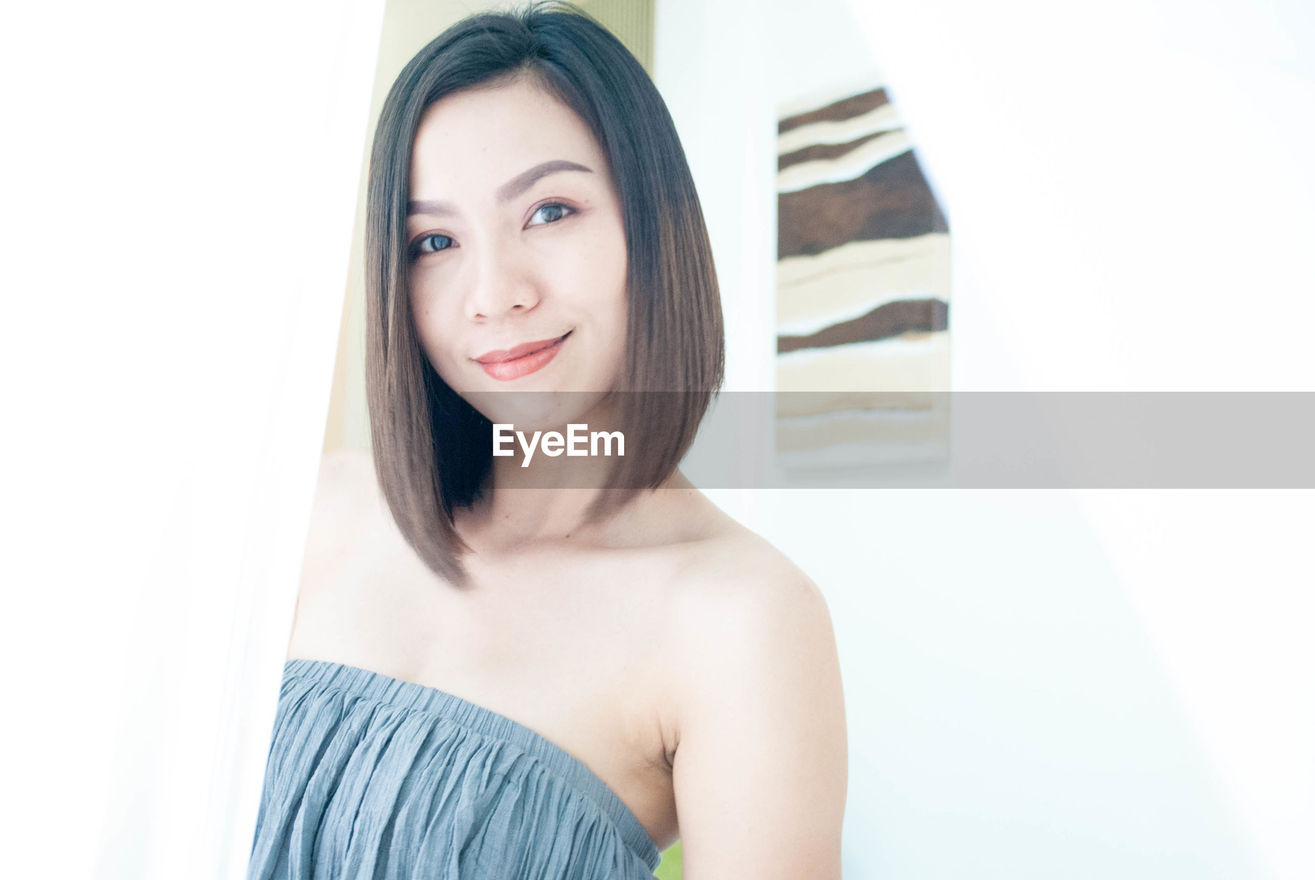 Portrait of beautiful young woman in off shoulder dress standing at home