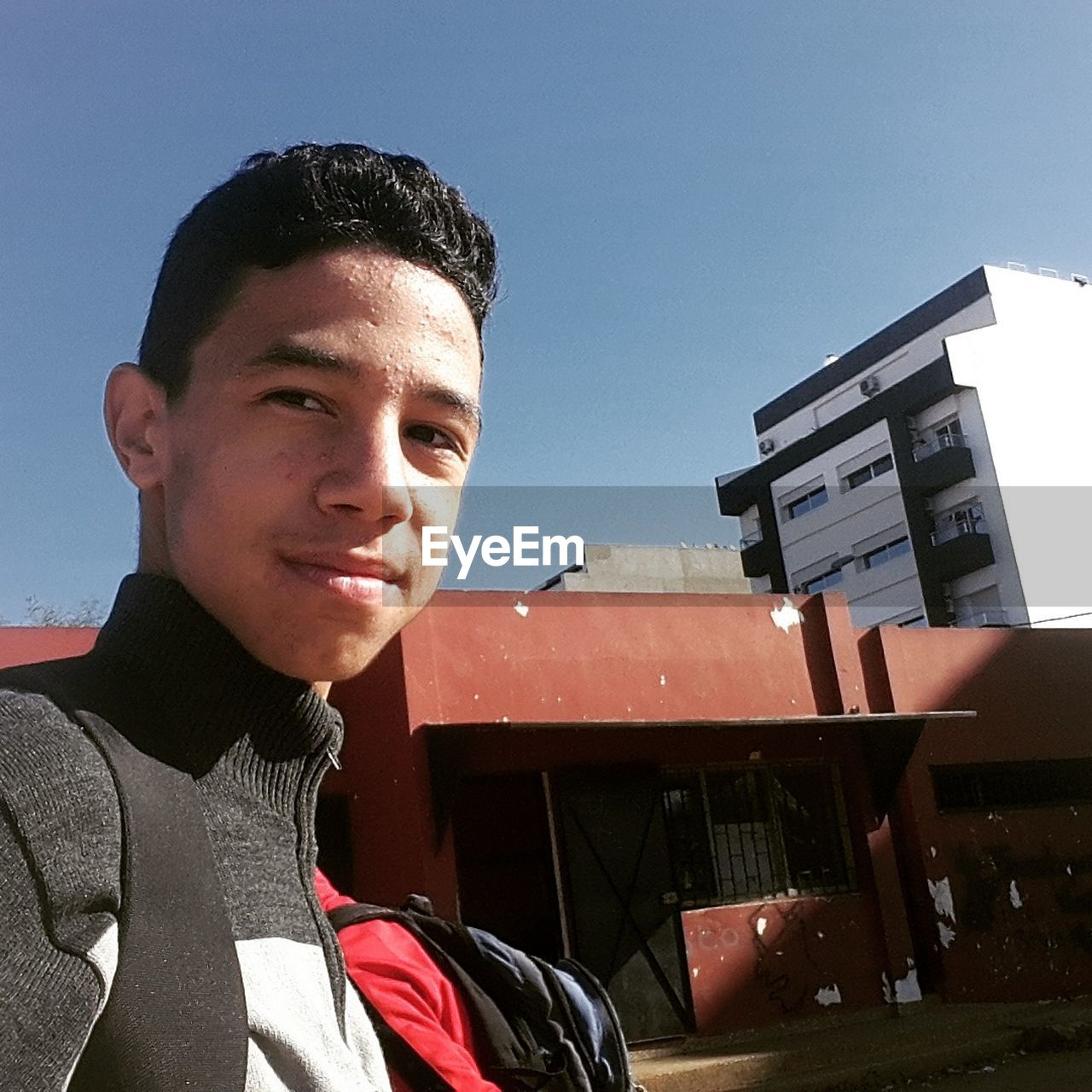 architecture, building exterior, built structure, real people, smiling, one person, outdoors, young adult, portrait, lifestyles, low angle view, looking at camera, sky, day, happiness, boys, clear sky