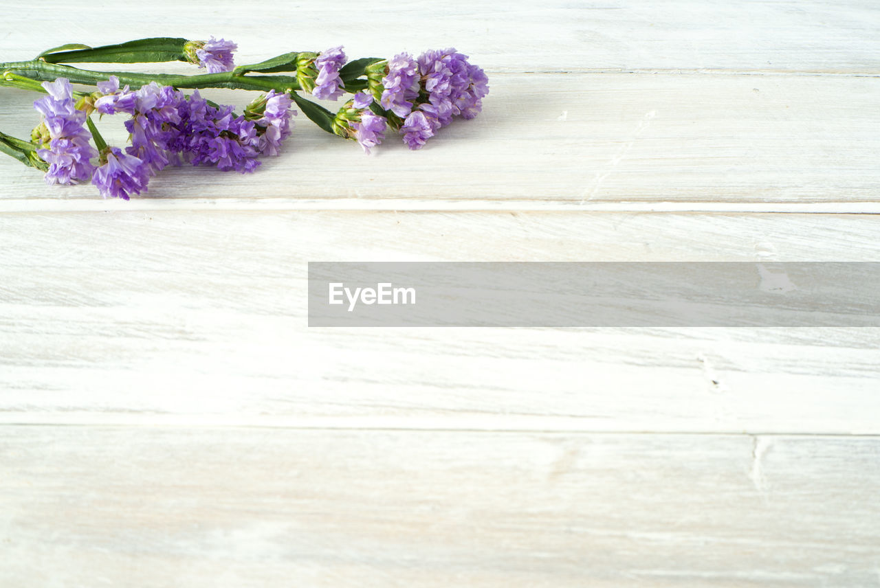 flower, flowering plant, plant, freshness, purple, vulnerability, fragility, table, wood - material, beauty in nature, indoors, no people, close-up, nature, petal, flower head, inflorescence, still life, high angle view, flooring, bunch of flowers, flower arrangement