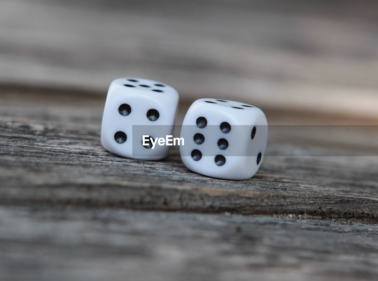 dice, leisure games, gambling, luck, arts culture and entertainment, opportunity, table, relaxation, still life, leisure activity, wood - material, close-up, selective focus, indoors, no people, spotted, cube shape, shape, two objects, high angle view, game of chance, surface level