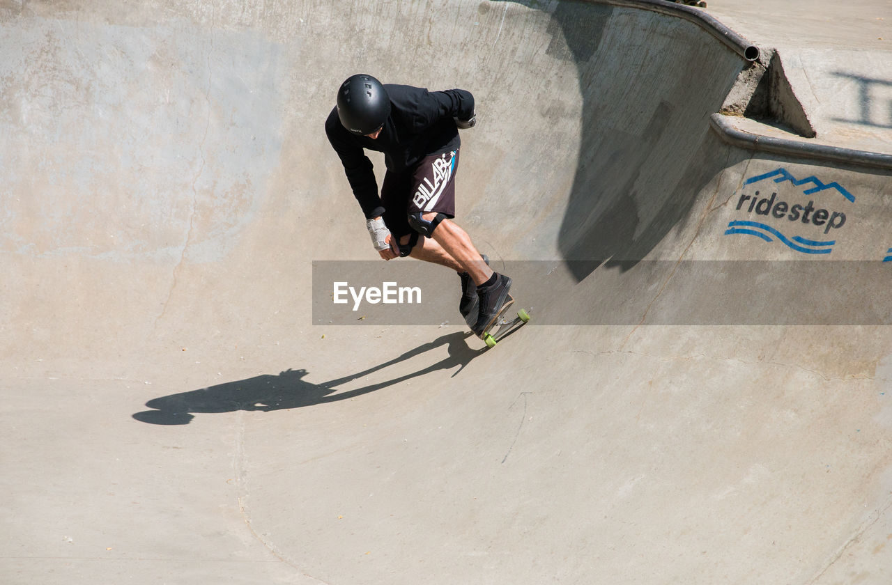 one person, skateboard park, sport, full length, real people, leisure activity, lifestyles, men, shadow, skill, extreme sports, day, sunlight, stunt, casual clothing, high angle view, sports ramp, nature, sports equipment, outdoors