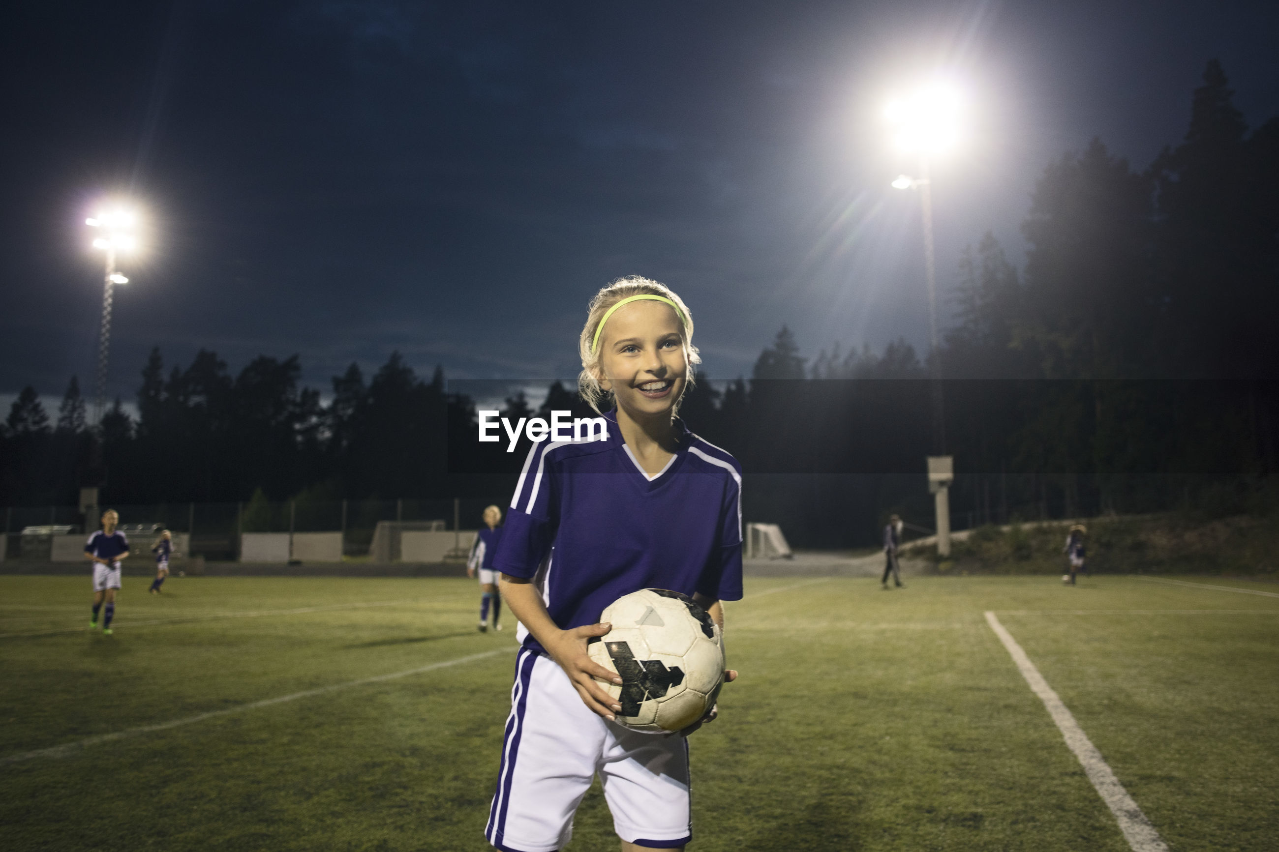 PORTRAIT OF SMILING YOUNG WOMAN STANDING ON SOCCER FIELD